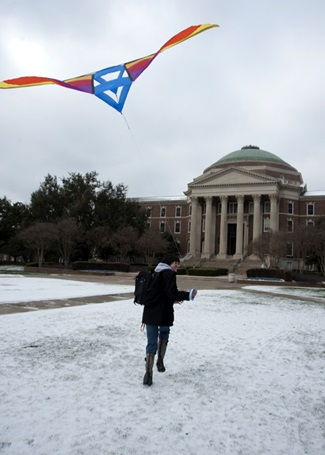 SMU student flying a kite in the snow on the main quad