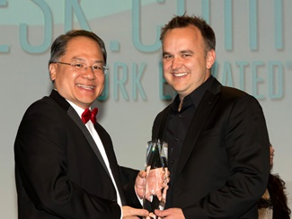 Simon Mak, associate director of the Caruth Institute for Entrepreneurship, presents the Dallas 100 award for fastest growing private company in North Texas to Jason McCann, CEO of Coppell-based VARIDESK.
