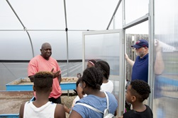 Horticulture expert Tyrone Day, left, talks with children about growing their own fresh vegetables.