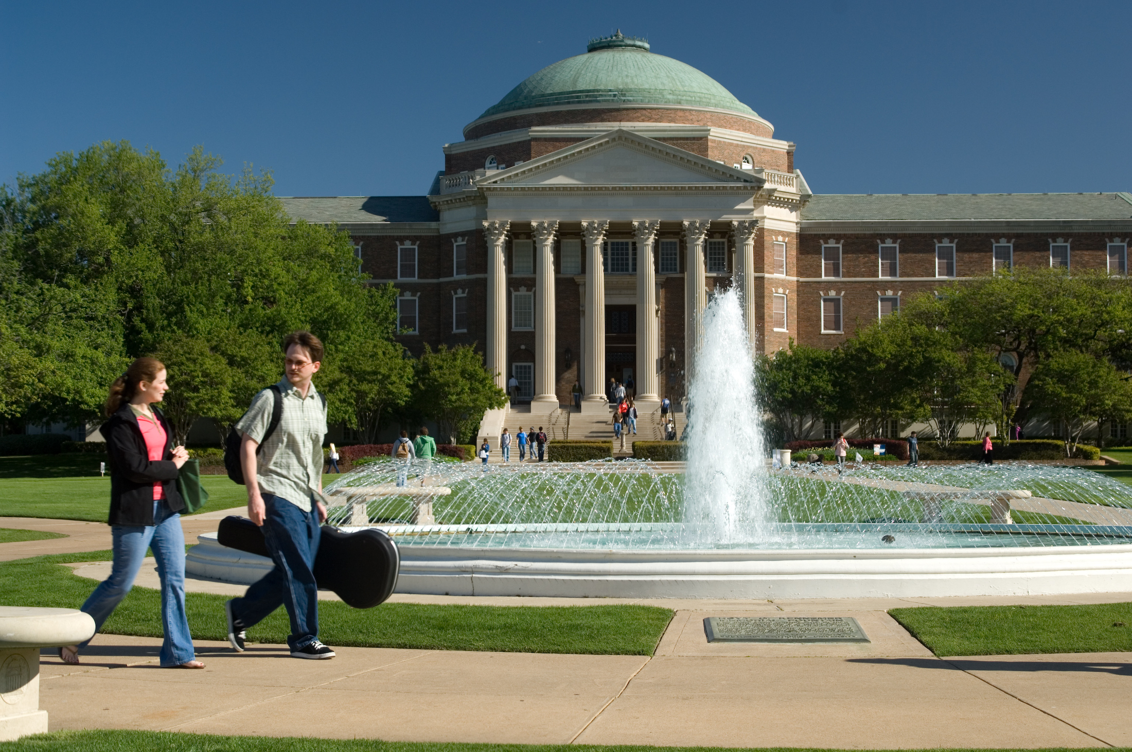 Students walk by the fountain with a view of Dallas Hall