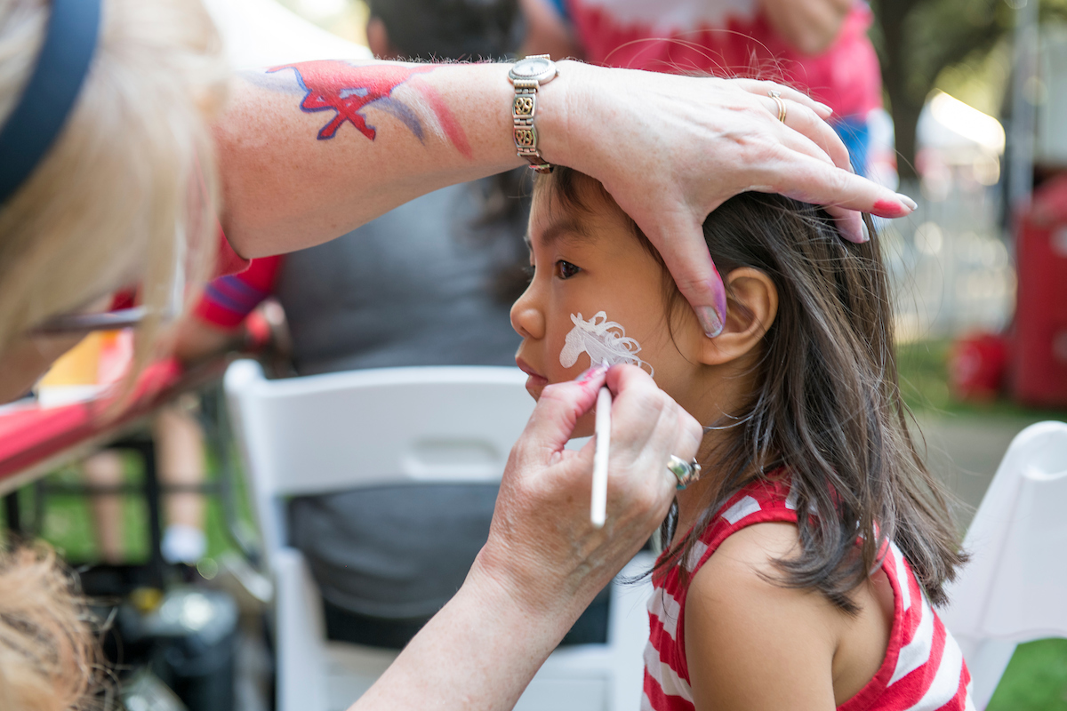 Child at face painting station