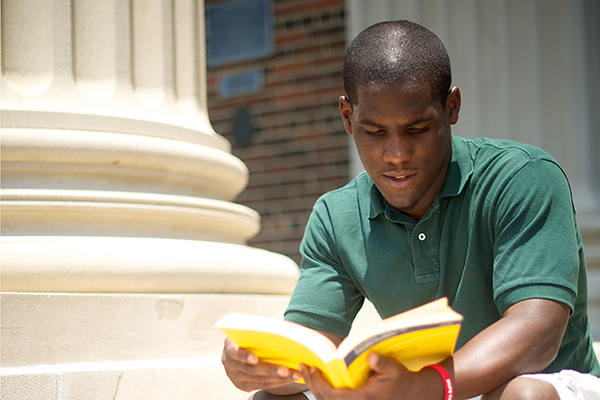 Student reading book on steps of Dallas Hall.