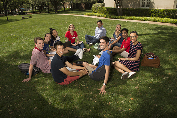 Group of students sitting down on grass.