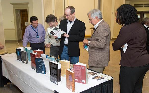 Group of people looking at books on a table.
