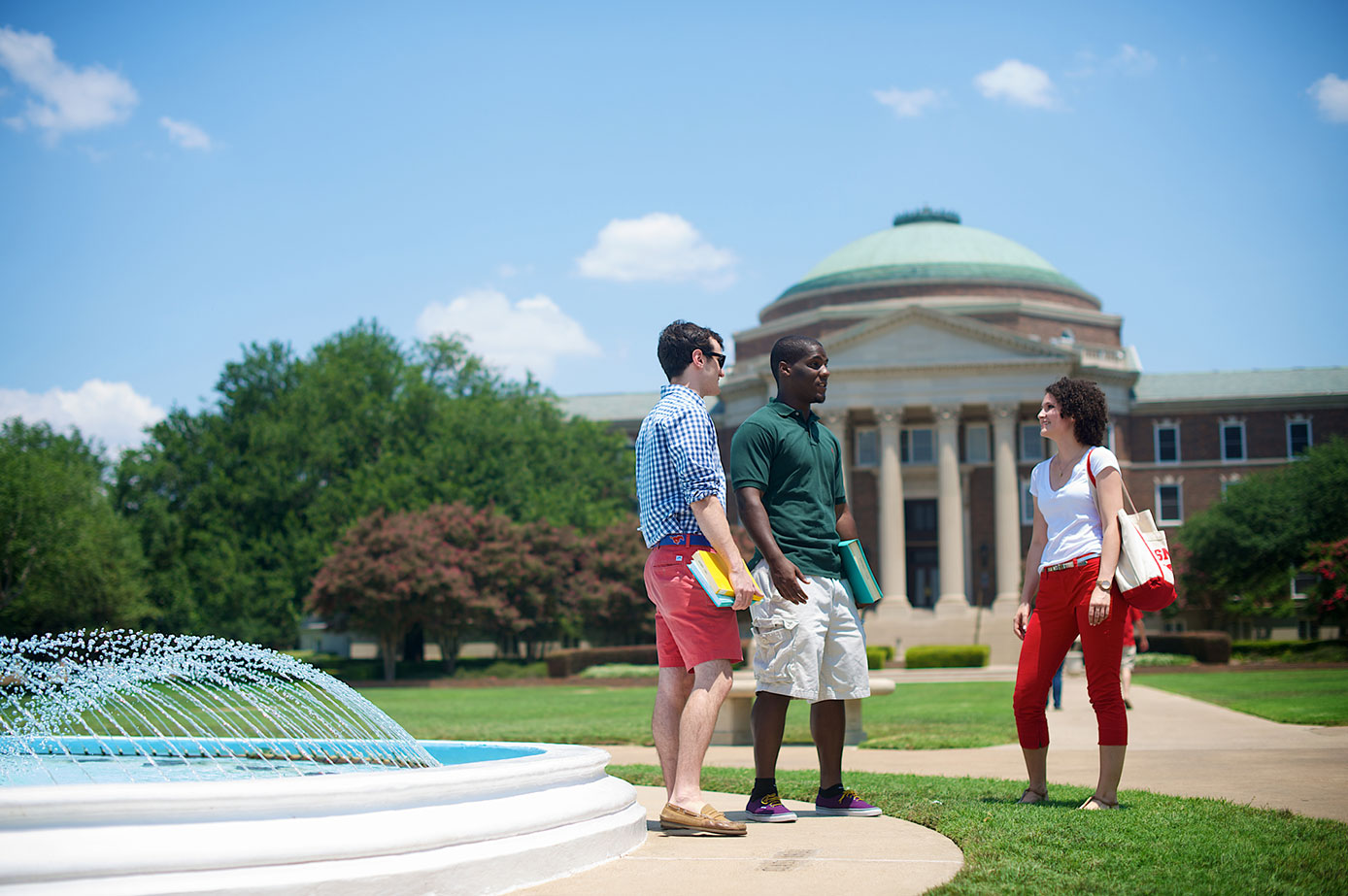Three students by a fountain, Dallas Hall in the background.