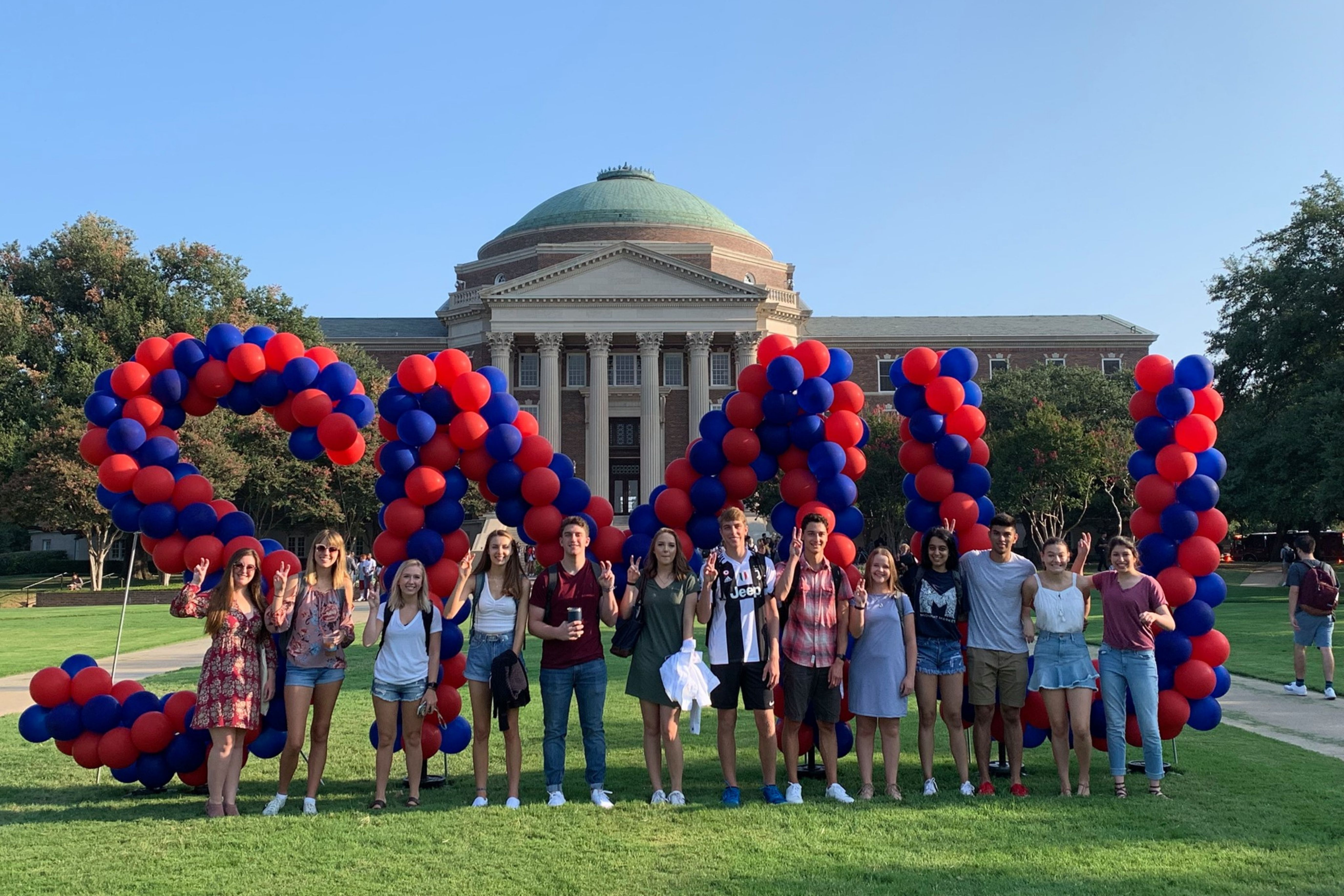 Students stand on Dallas Hall Lawn in front of red and blue SMU balloons.