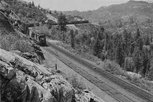 Southern Pacific No. X8406 mixed freight is eastbound passing below Crystal Lake formerly used by SP for watering steam locomotives. [No. 1]