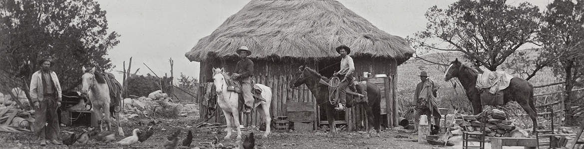 owboys in front of small house with thatch roof on ranch, ca. 1900