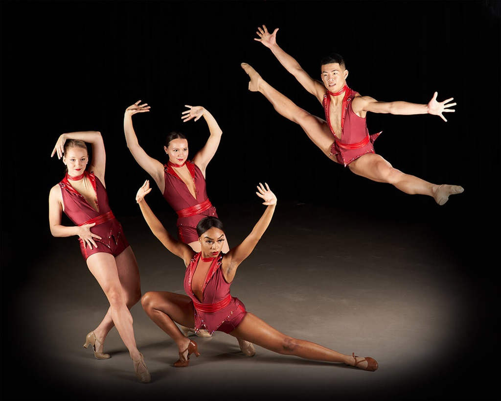 Dancers in red outfits dancing against a black background