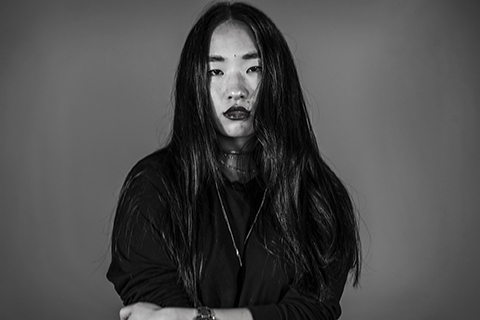 asian girl not smiling in black and white photo on gray background