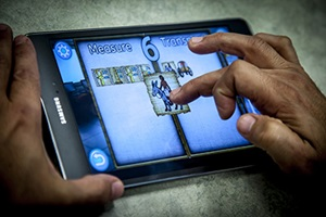 XPRIZE, People With Words. A person playing lost Codex: Lost World of Atlantis using a mobile device.