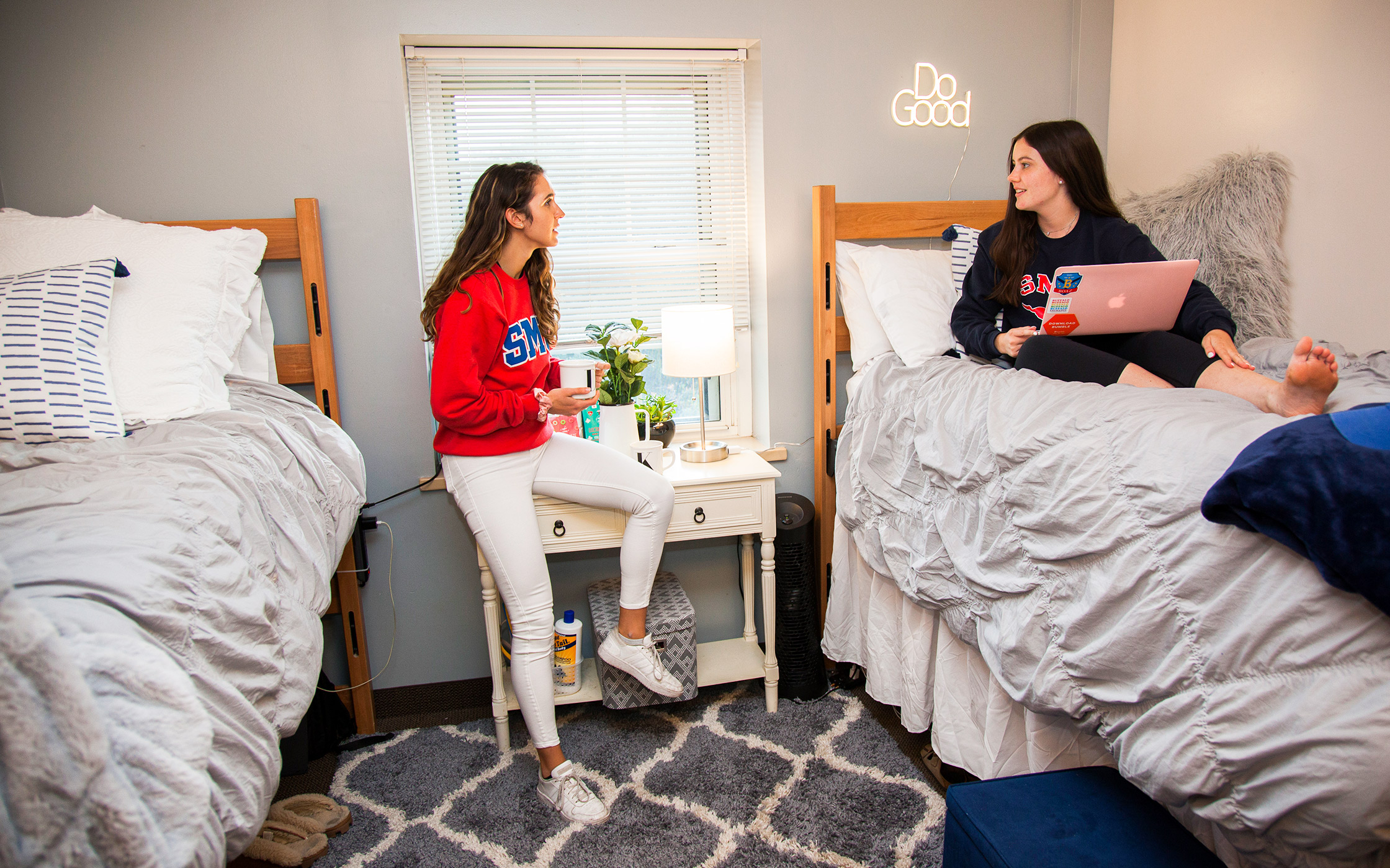 Two students in their SMU Residential Commons sitting on their bed and talking
