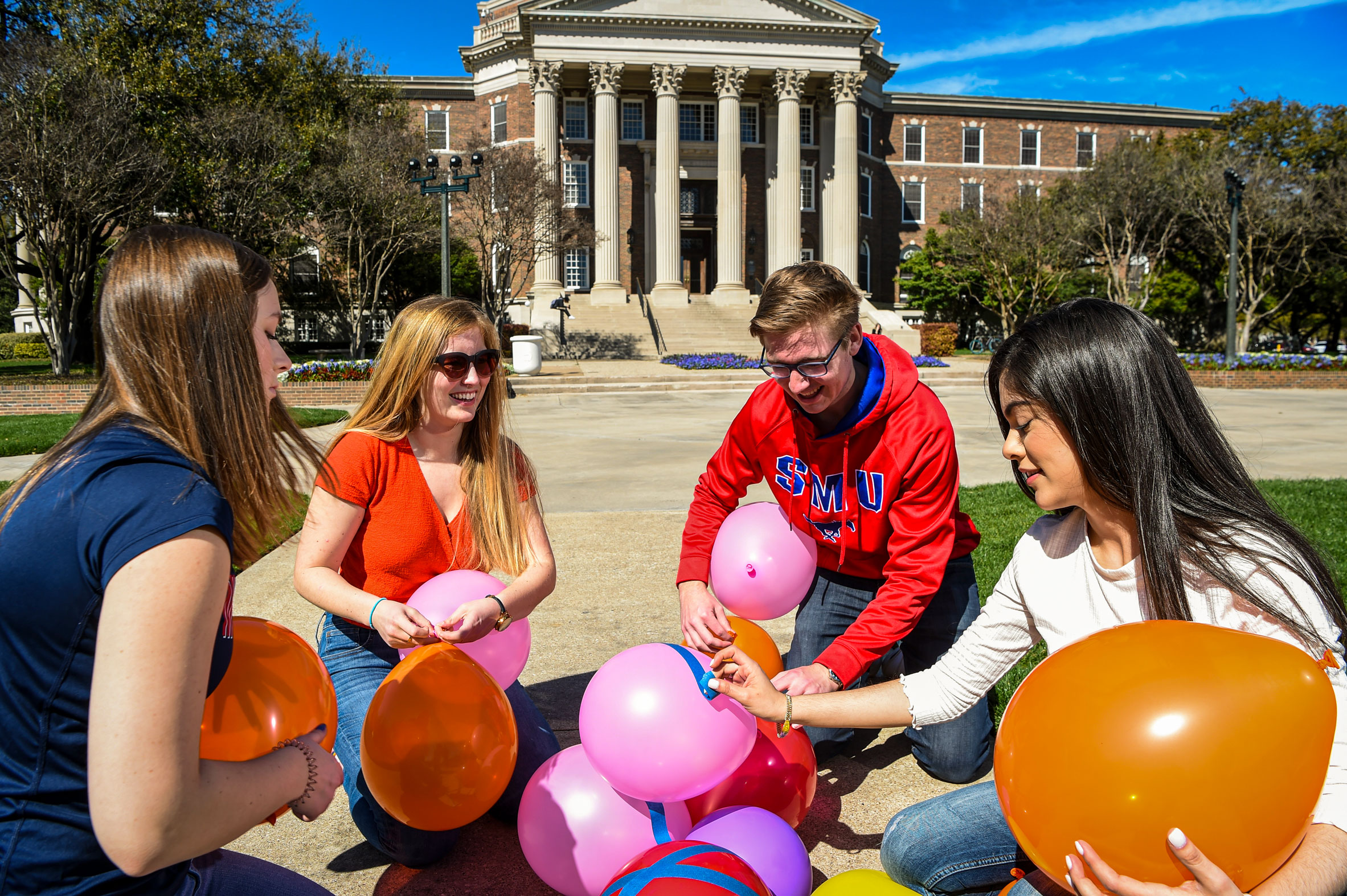 Four students working together to build a tower of balloons on Dallas Hall lawn.