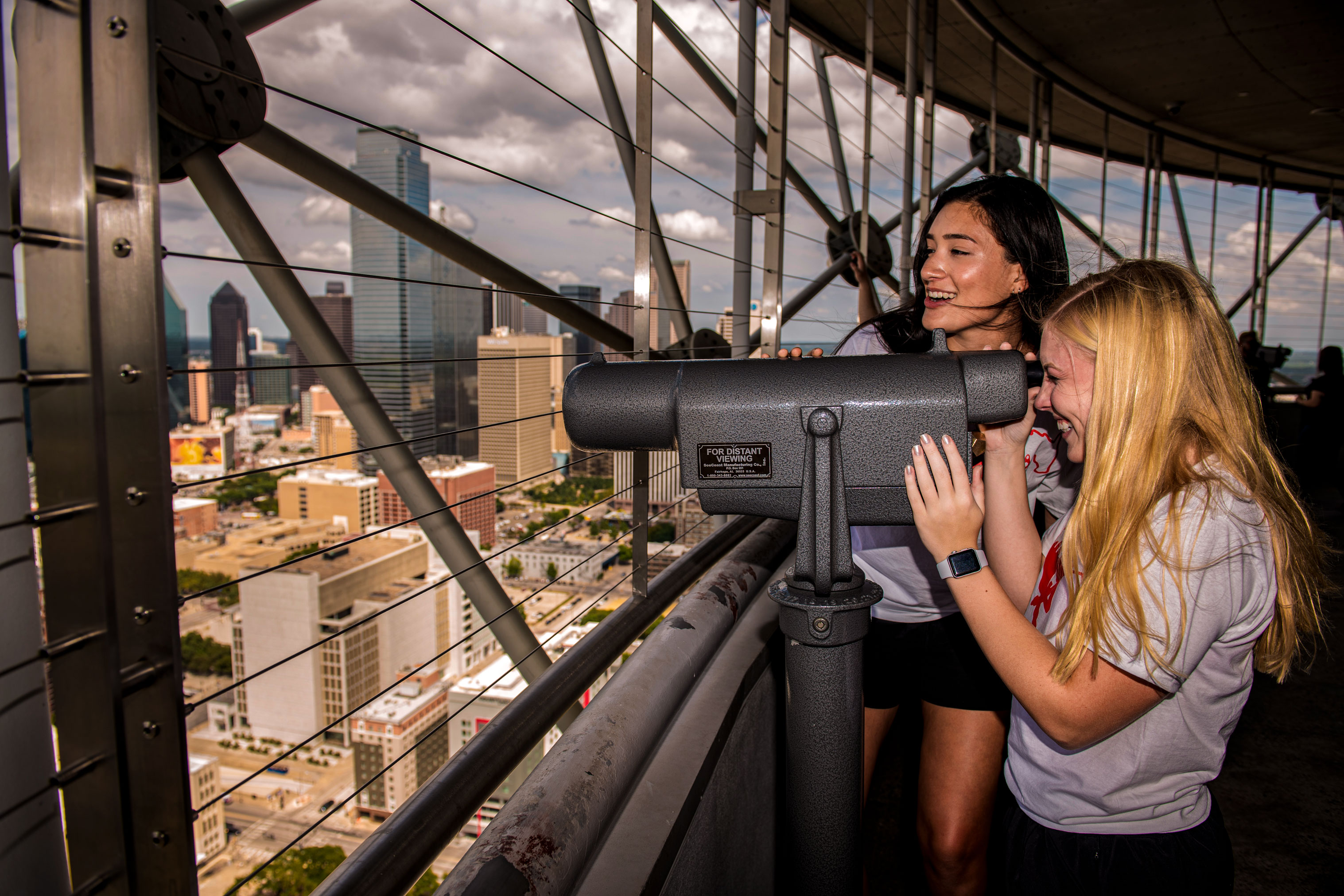 Students look out at Dallas skyline through a telescope at Reunion Tower