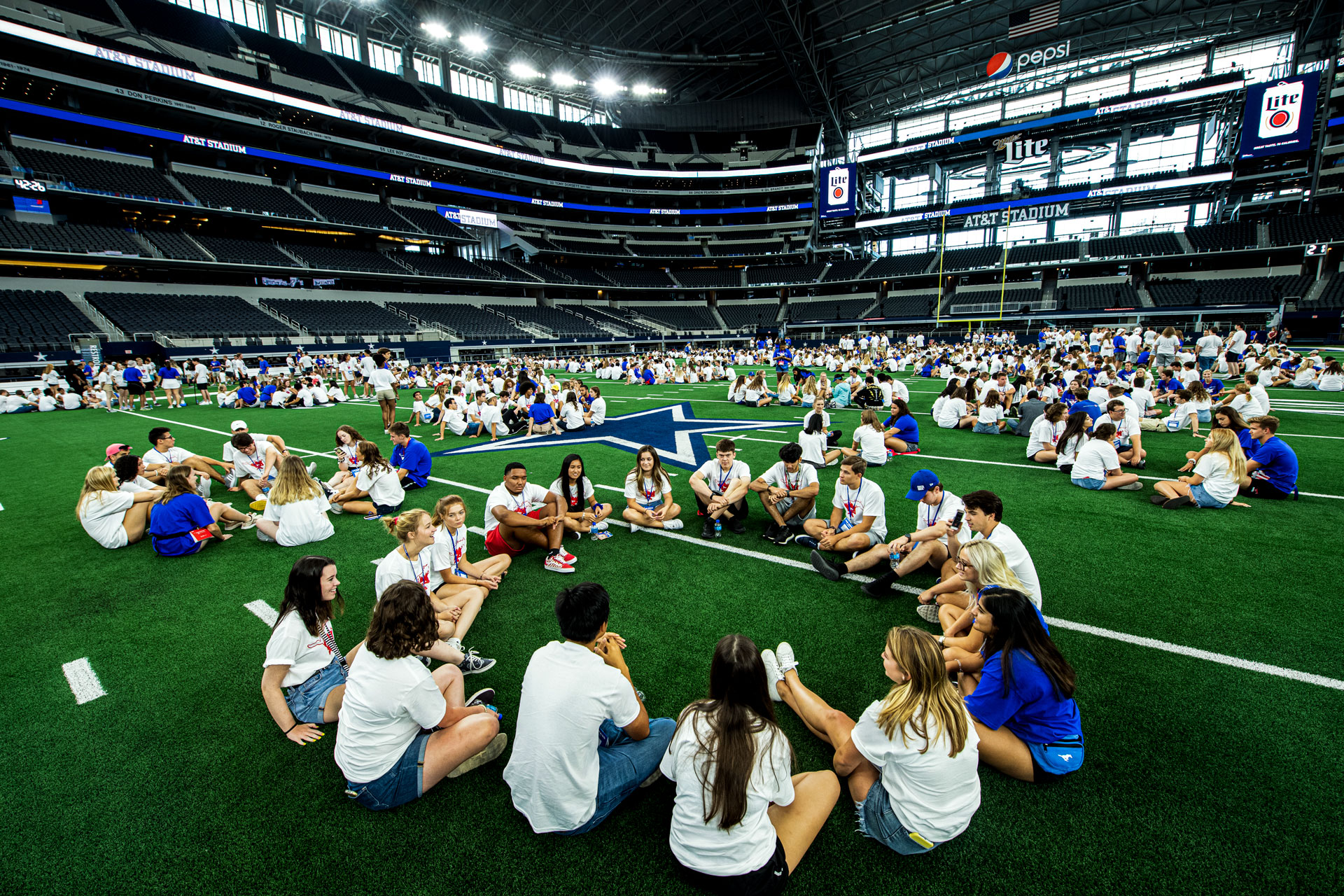 Students in small groups at Cowboys Stadium during Stampede