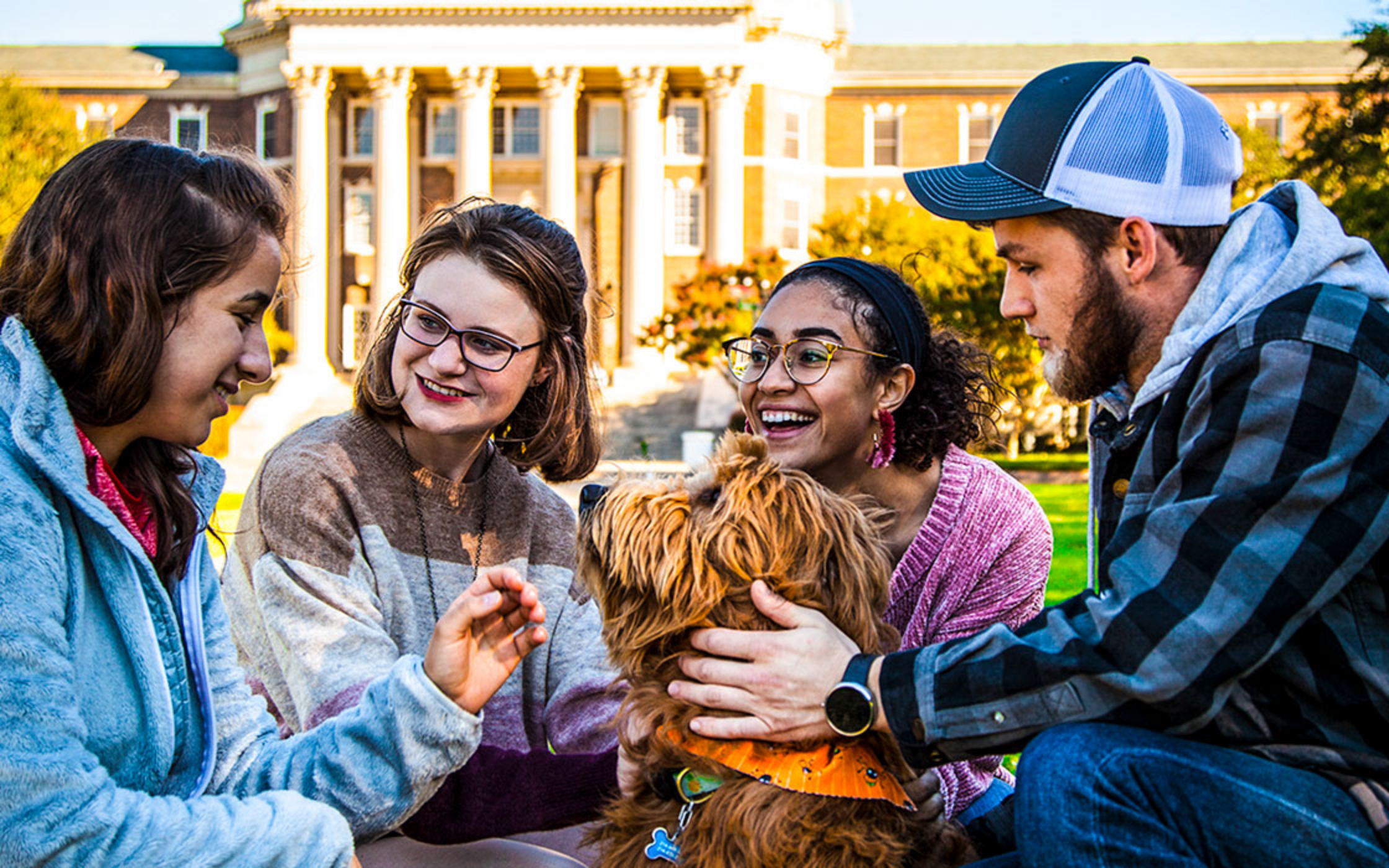 Group of people sitting with a dog on the front lawn of Dallas Hall