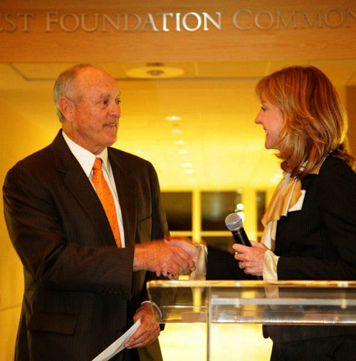 SMU Cox Assistant Dean of Marketing and Communications Lynda Oliver congratulates baseball hall of famer Nolan Ryan on being named 2012 CEO of the Year at the unveiling ceremony held at the Collins Center.