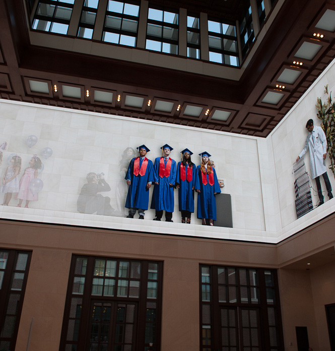 The Bush Center's Freedom Hall features a 360-degree, high-definition video wall showing images of people at work and play. This image shows four college graduates wearing, not surprisingly, SMU blue and red.