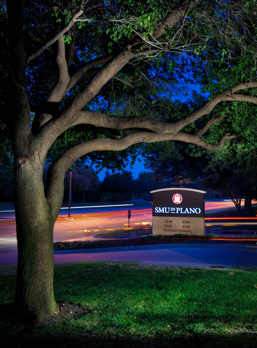 night shot of SMU in Plano sign looking from campus out to street